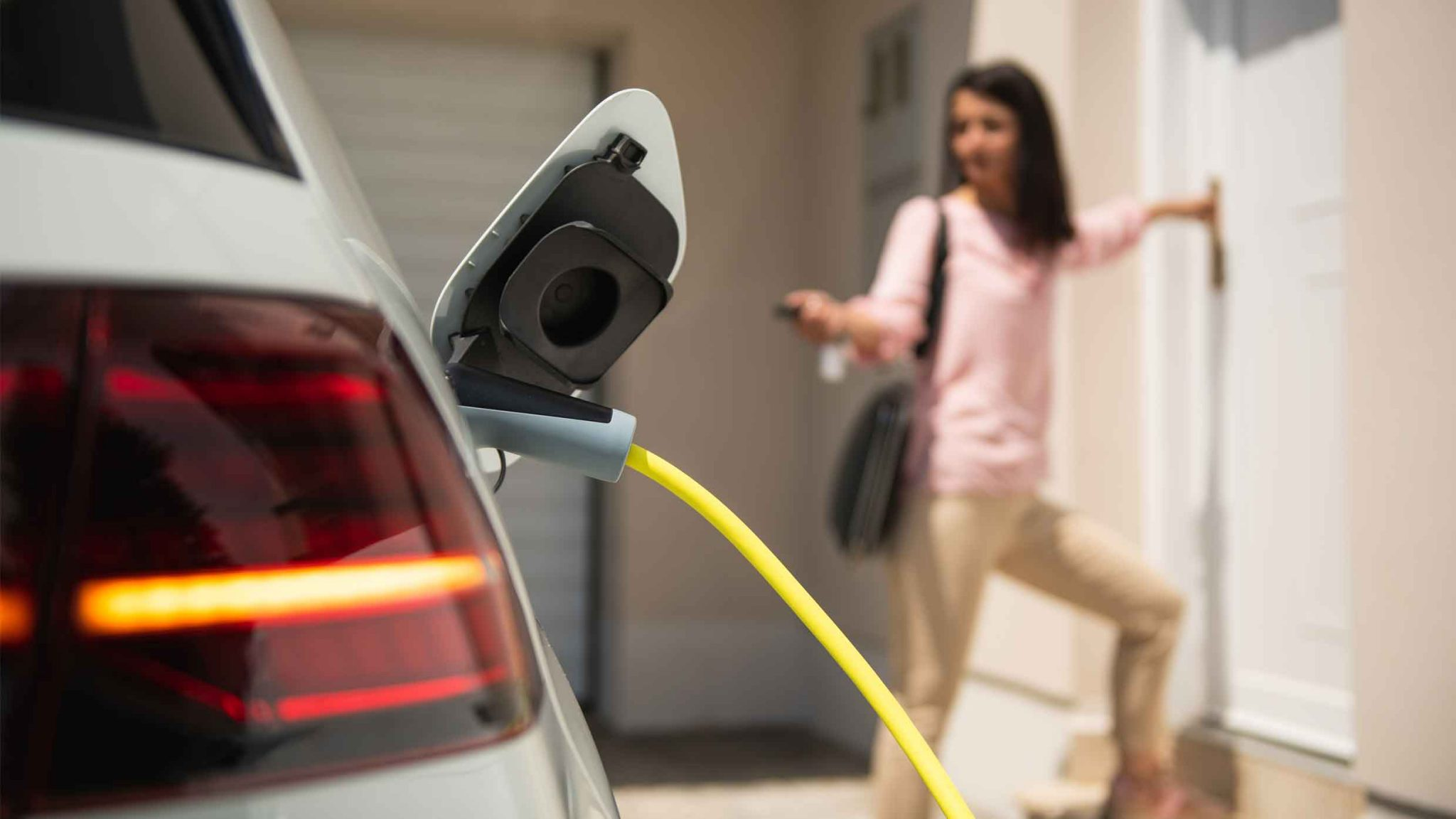 Ev charging with Woman entering her home