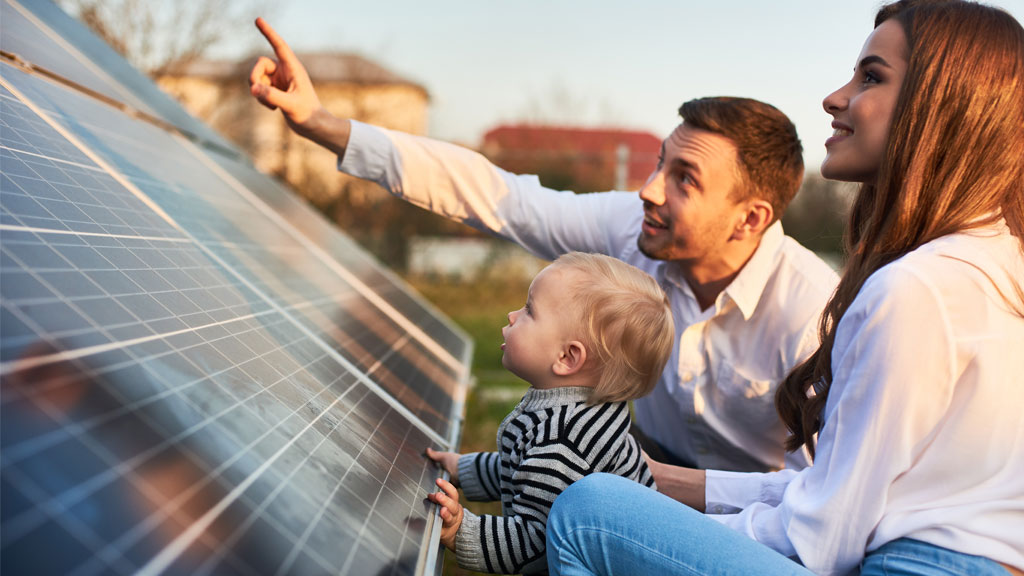 Family looking up at solar panels