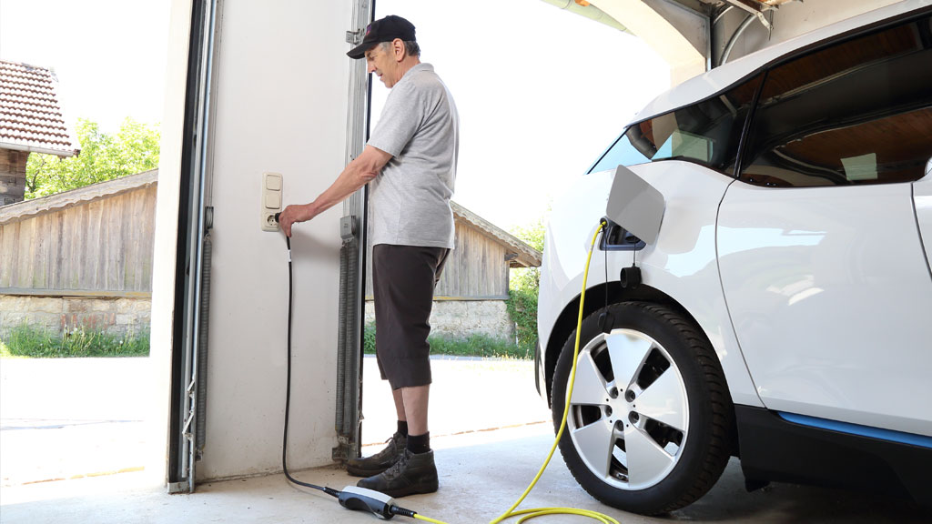 Man plugging in ev charger in his garage