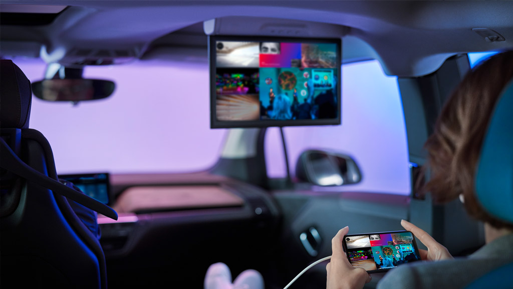A BMW i3 with a womaen using the infotainment system