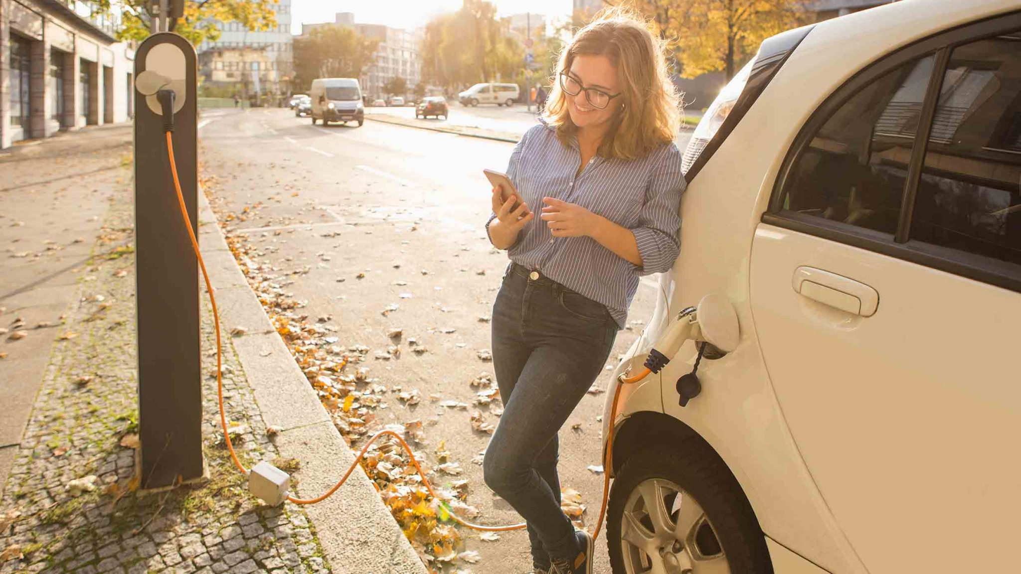 Person leaning against electric car looking at phone as the EV charges.economic and environmental benefits of an EV