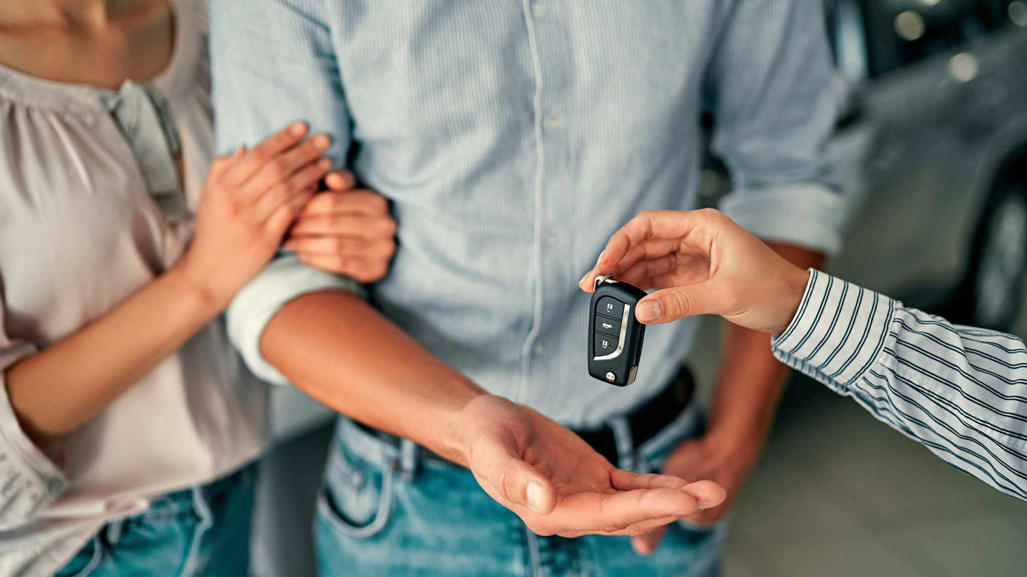 Couple being handed keys to car