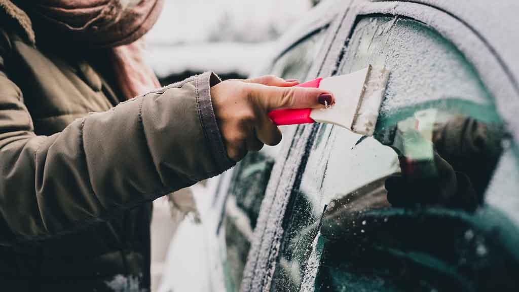 Person scraping Ice of their Car