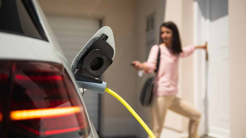 Home charging EV with person in background