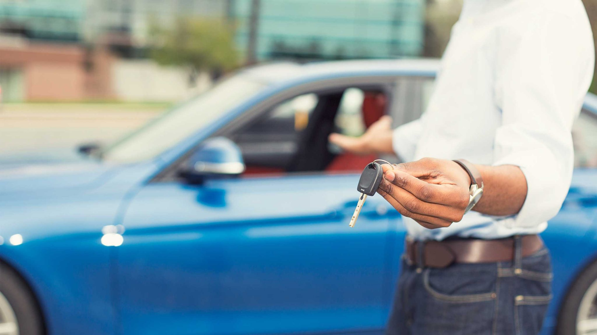 A Man holding the key to a new EV