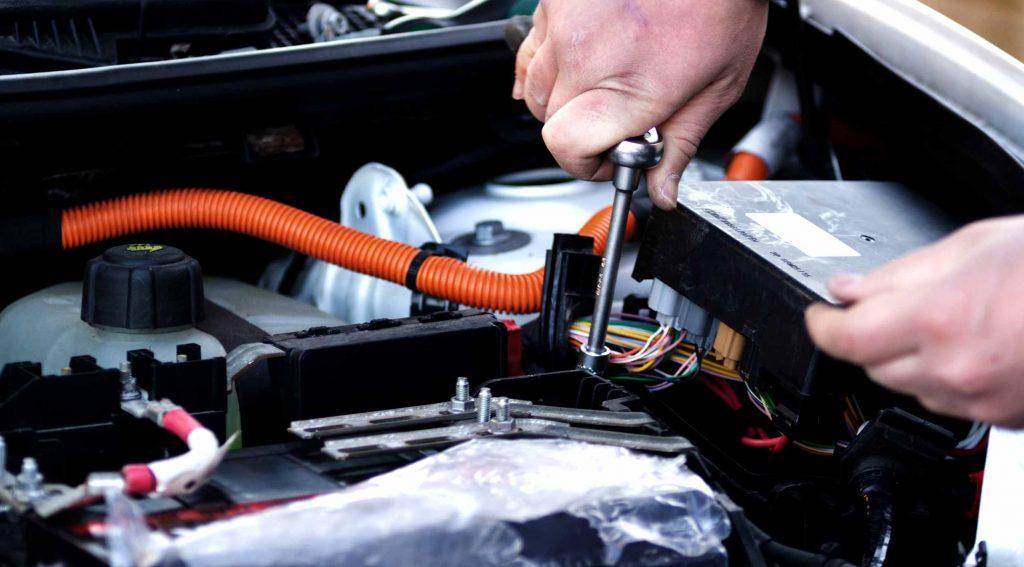 A man servicing an EV
